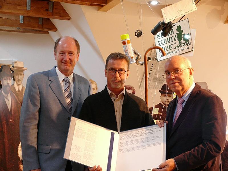 v.l.n.r.: H. Höper (Vorsitzender Naturparkregion Lüneburger Heide e.V.), M. Fasel (i.A. des Europarat vor Ort), W. Holtmann (Vorsitzender des VNP) mit dem 1. Diplom von 1967