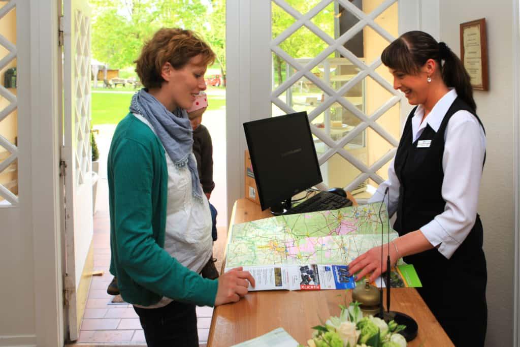 Hotelfachfrau berät einen Gast im Hotel Hof Tütsberg bei Schneverdingen